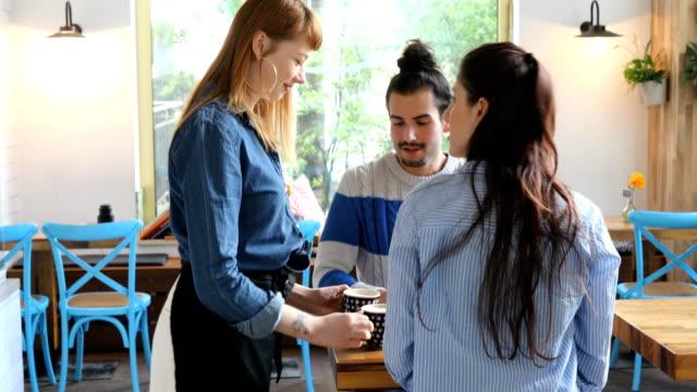 Jungen Barista Kaffee paar im Cafe serviert