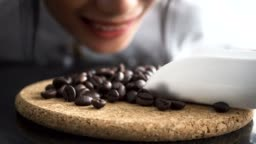 Young barista smelling coffee beans laying on table with smiley face