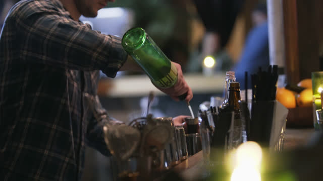 stockvideo's en b-roll-footage met young bartender pours lime juice into craft cocktail in popular chicago bar. - bar tapkast