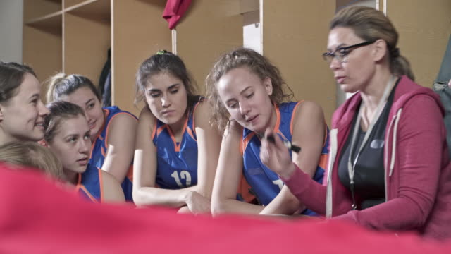Young basketball girls talking with coach in locker room