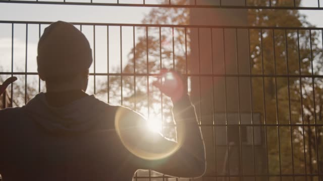 young basketball player at fence after practice - recinzione video stock e b–roll