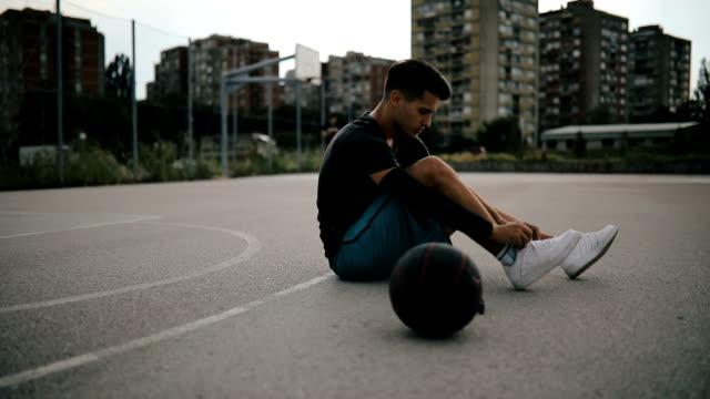 vídeos de stock, filmes e b-roll de jovem basquetebolista amarra para baixo de cadarço - laço acessório
