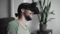 Young bearded hipster man using his VR headset display for watching the 360 video and feels as he is on a concert or disco while sitting on sofa at home in the living room. VR Technology.