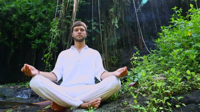 Young bearded man doing yoga meditation near waterfall