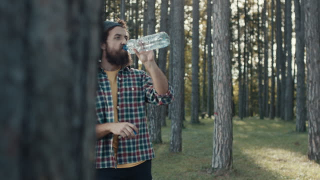 young bearded man drinking alcohol at park - comedian stock videos & royalty-free footage