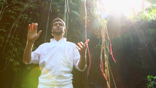 Young bearded man meditating in a jungle