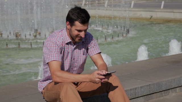 young bearded man uses smartphone for messages sitting near the fountain - 30 34 years video stock e b–roll