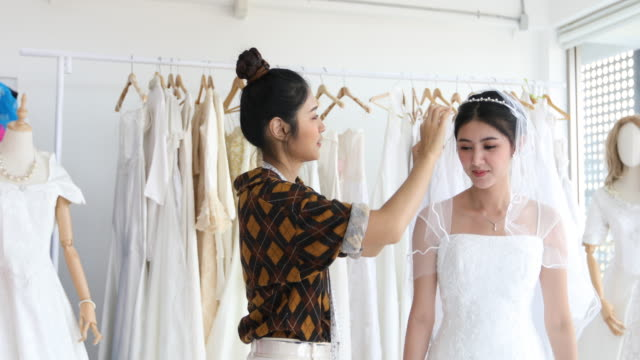 young beautiful asian bride woman is standing in front of mirror and fitting dress in atelier with fashion designer for wedding at clothing store - wedding dress stock videos and b-roll footage