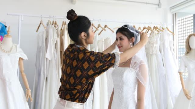 Junge schöne asiatische Braut Frau vor Spiegel steht und passende Kleid im Atelier mit dem Modedesigner für Hochzeit im Bekleidungsgeschäft