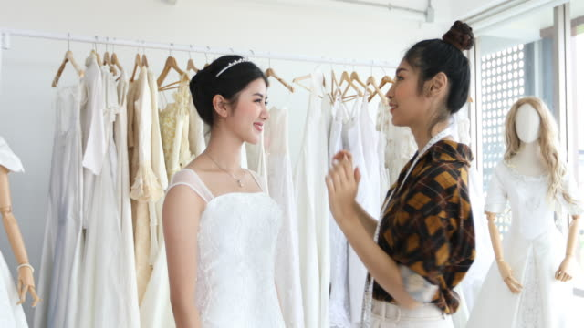 young beautiful asian bride woman is standing in front of mirror and fitting dress in atelier with fashion designer for wedding at clothing store - designer clothing stock videos & royalty-free footage