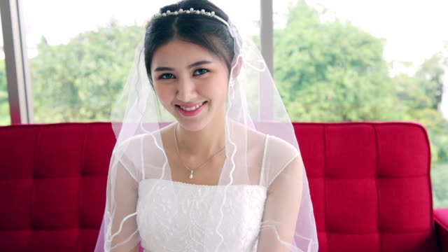 young beautiful asian bride woman ready for wedding sitting on sofa and smiling with shy on her face - bride stock videos & royalty-free footage