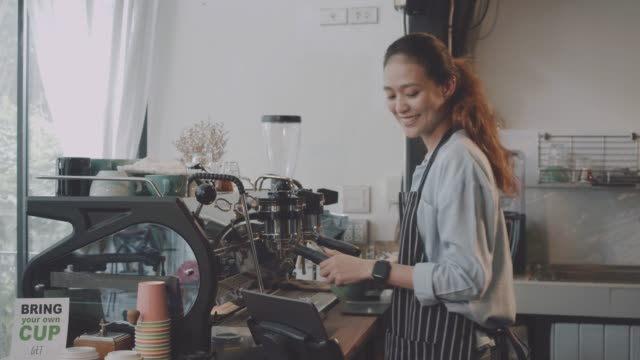 若い美しいアジアの女性バリスタは、笑顔のコーヒーショップのバーカウンターでお客様に提供されたホットコーヒーカップを保持するエプロンを着用します。カフェとコーヒーショップの� - 外食産業関係の職業点の映像素材/bロール