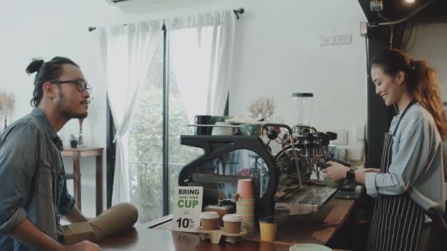 若い美しいアジアの女性バリスタは、笑顔のコーヒーショップのバーカウンターでお客様に提供されたホットコーヒーカップを保持するエプロンを着用します。カフェとコーヒーショップの� - カフェテリア点の映像素材/bロール
