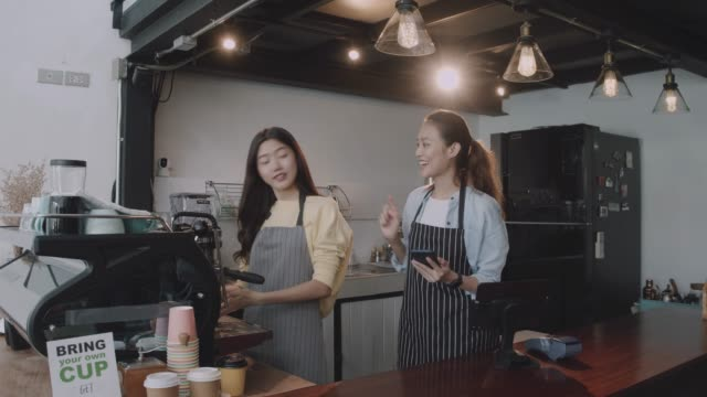 vídeos de stock e filmes b-roll de young beautiful asian woman barista wear apron using smartphone selfie with friend at bar counter in coffee shop with smile face.concept of cafe and coffee shop small business. - empregada de mesa