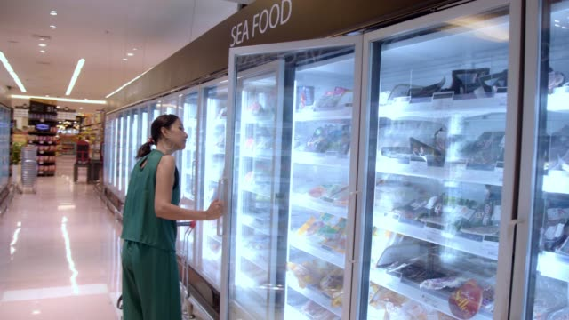 Young Beautiful Asian Woman Buying Fresh Frozen Seafood at the Grocery Store Supermarket.