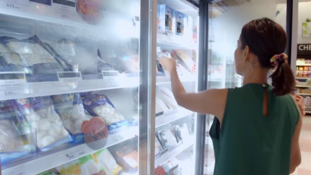 vídeos de stock e filmes b-roll de young beautiful asian woman buying fresh frozen seafood at the grocery store supermarket. - congelado