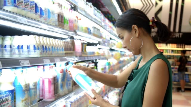 young beautiful asian woman choosing and shopping molk in the grocery store supermarkt. - milk stock-videos und b-roll-filmmaterial
