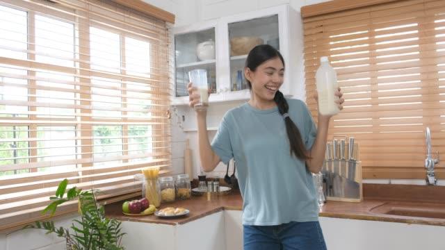 Jeune femme asiatique belle potable de lait et dansant dans la cuisine, des modes de vie sains heureux