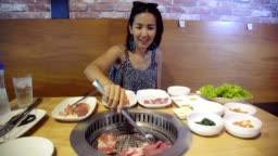 Young Beautiful Asian Woman Grilling Barbecue Grill on Korean Pan. Closeup Pork Slice grilled in Korean Restaurant.