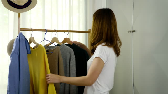 vídeos de stock e filmes b-roll de young beautiful asian woman searching clothes in the wardrobe closet at home - coleta seletiva