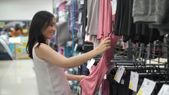 young beautiful asian woman shopping clothes in a clothing store - only teenage girls stock videos and b-roll footage