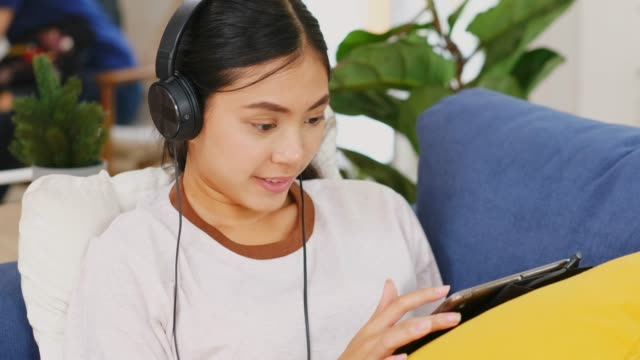 vídeos de stock e filmes b-roll de young beautiful asian woman using digital tablet and headphones listing to music while sitting on sofa at home living room, people and technology, generation z lifestyles - generation z