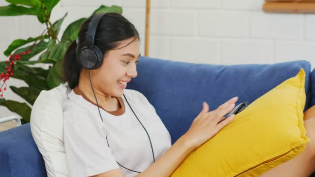 vídeos de stock e filmes b-roll de young beautiful asian woman using digital tablet and headphones while sitting on sofa at home living room, people and technology, generation z lifestyles - generation z