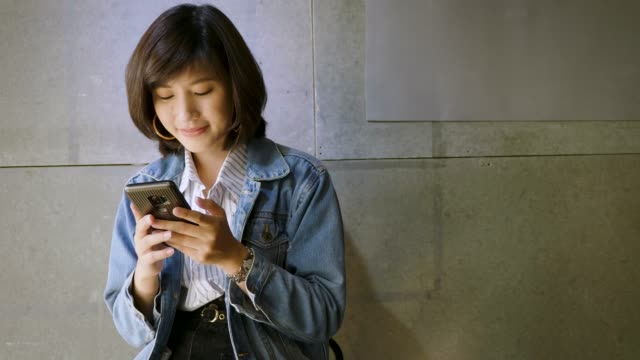 Young beautiful Asian woman using smart phone and looking at camera on concrete gray background at office