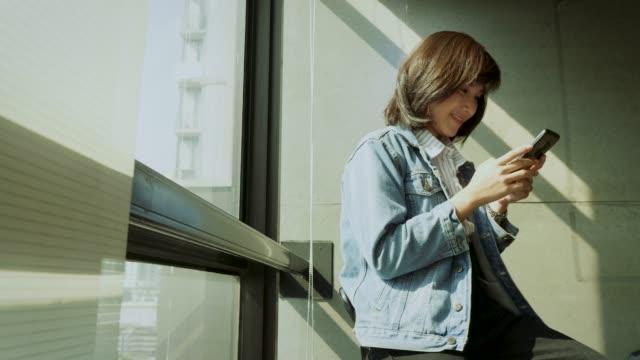 オフィスの窓の隣にスマートフォンを使用して若い美しいアジアの女性 - 学生点の映像素材/bロール