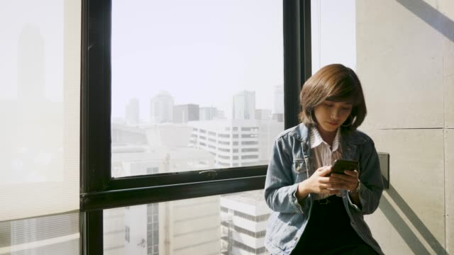 Young beautiful Asian woman using smart phone next to window at office