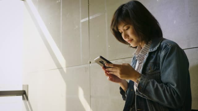 Young beautiful Asian woman using smart phone on concrete gray background at office