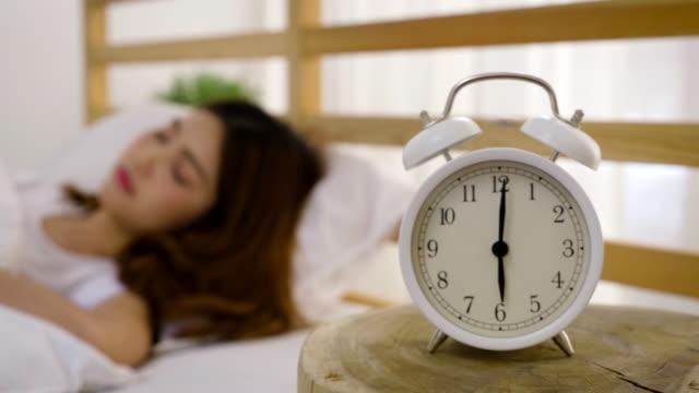 若いの美しいアジアの女性を自宅、概念を覚ます目覚まし時計彼女のベッドで目を覚ます - 東洋民族点の映像素材/bロール