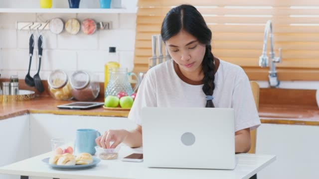 young beautiful asian woman working with laptop computer and eating snack in kitchen at home, people and technology, working at home, online education - e learning stock videos & royalty-free footage