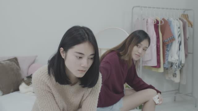 stockvideo's en b-roll-footage met jonge mooie aziatische vrouwen lesbische paarminnaar die na conflict elkaar in bedkamer thuis met humeurige emotie heeft beklemtoond. concept van lgbt seksualiteit met overstuur en ongelukkige levensstijl samen. - overstuur
