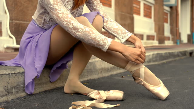 young beautiful ballerina puts on pointe shoes along the street - ballet dancer stock videos & royalty-free footage