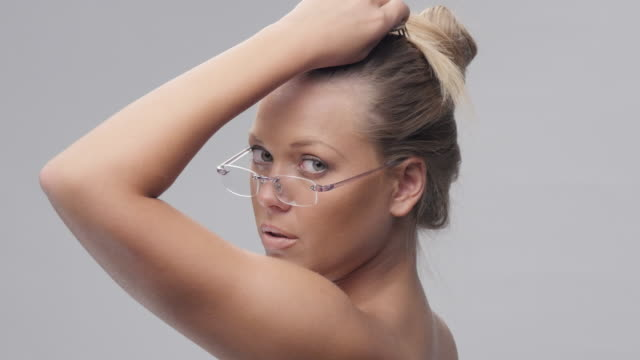 Young Beautiful Blond Woman With Glasses looking at Camera and Flirting.