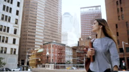 Young beautiful businesswoman holding the documents and walking to work in financial district of New York. Slow motion