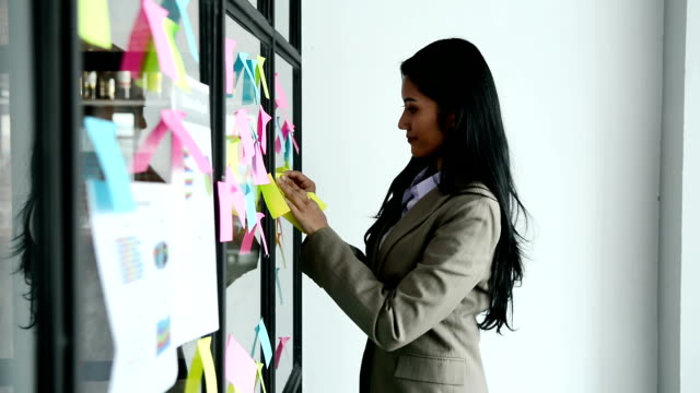young beautiful businesswoman putting post-it note paper on the mirror glass at modern office - whiteboard stock videos & royalty-free footage