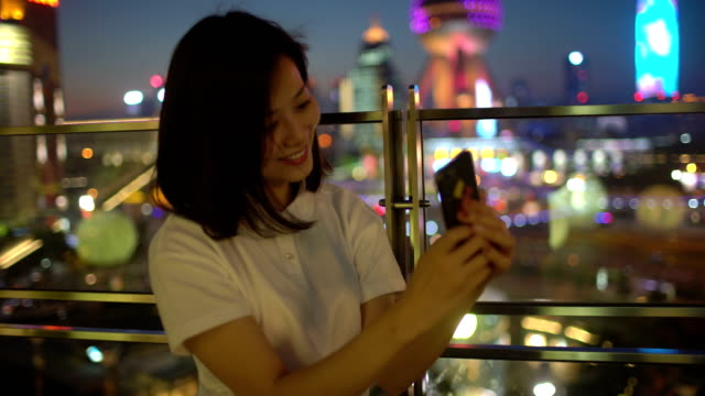 young beautiful Chinese woman doing selfie in the Shanghai night