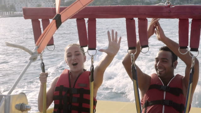 Young Beautiful Couple Doing Parasailing