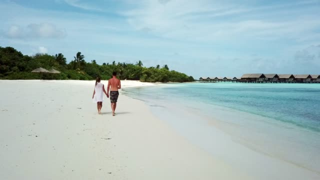 young beautiful couple walking on a white sandy beach on the maldives - exoticism stock videos & royalty-free footage