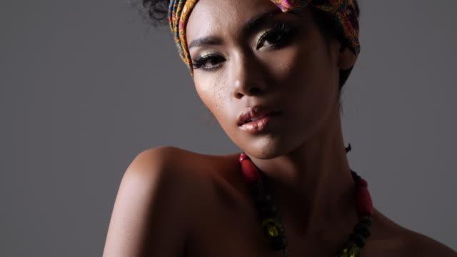 vidéos et rushes de jeune mannequin beau style africain traditionnel avec foulard, boucles d'oreilles et le maquillage sur fond sombre. portrait du côté vue du modèle de peau sombre sur un fond noir dans les coulisses. ombre et lumière portrait d'une femme en vue de c - coiffure afro
