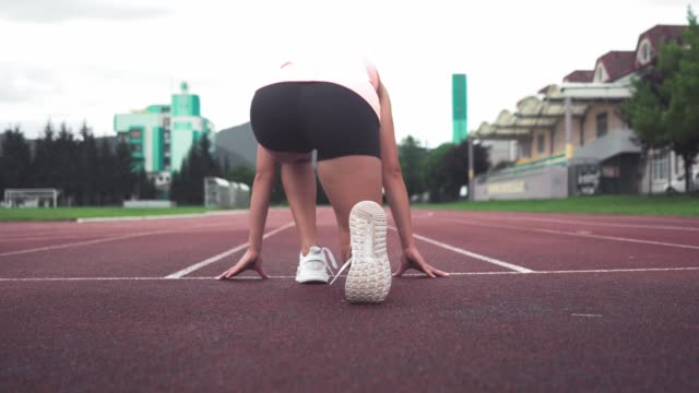 stockvideo's en b-roll-footage met jonge mooie vrouwelijke atleet doen sprint - dameskleding