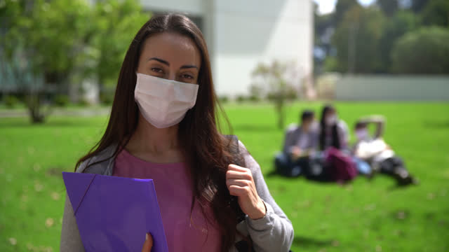 vídeos de stock, filmes e b-roll de jovem linda estudante segurando um caderno e mochila no ombro de frente para a câmera usando uma máscara facial protetora - máscara