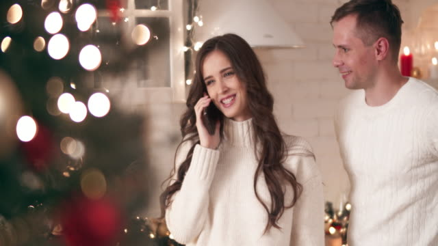 young beautiful girl congratulates her friends and parents on christmas holidays on the phone. her boyfriend is next to her. - month stock videos & royalty-free footage