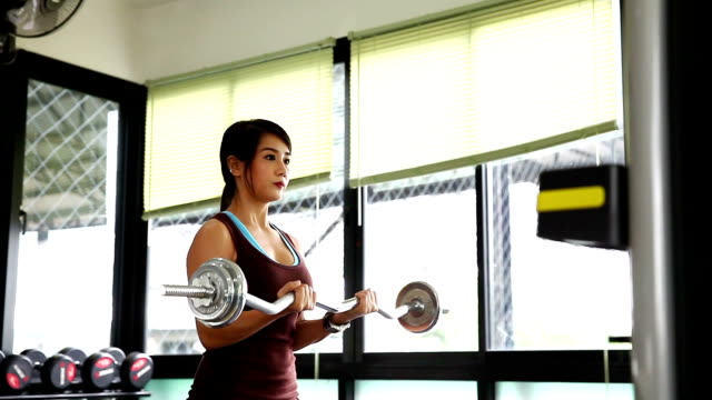 young beautiful girl in the gym doing exercises with barbell - weight training stock videos & royalty-free footage