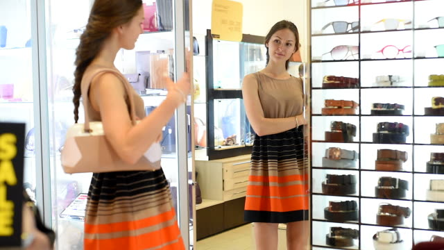 young beautiful girl in the mirror trying on bag