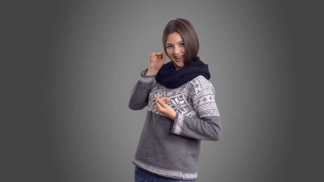 young beautiful girl in winter sweater show copy space - gray background stock videos and b-roll footage