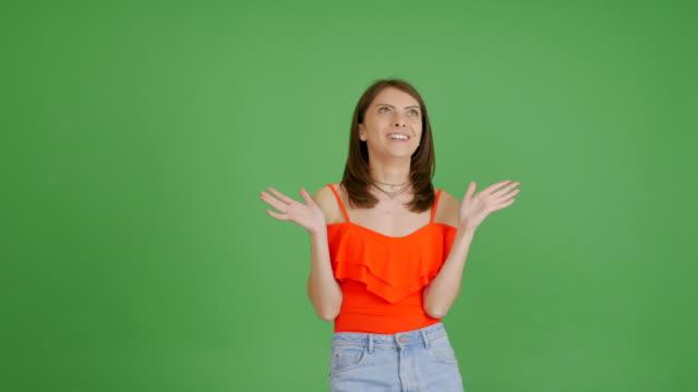 vidéos et rushes de jeune belle fille est surprise par quelque chose sur un fond vert - vêtement de peau
