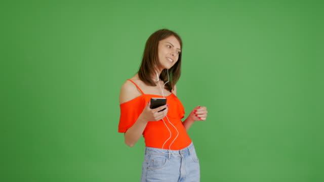 vídeos de stock, filmes e b-roll de linda menina ouvindo música no telefone sobre um fundo verde - foto de estúdio